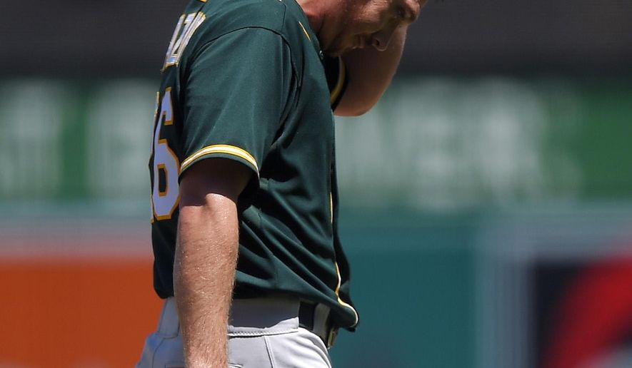 Oakland Athletics starting pitcher Scott Kazmir rubs his head after being taken out of a baseball game during the second inning against the Los Angeles Angels, Sunday, Aug. 31, 2014, in Anaheim, Calif. Kazmir walked in two runs during the inning. (AP Photo/Mark J. Terrill)