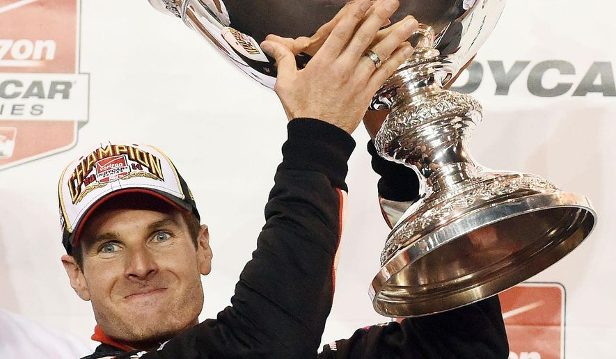 Will Power holds the Astor Cup after winning the IndyCar Series season championship Saturday, Aug. 30, 2014, at Auto Club Speedway, in Fontana, Calif. (AP Photo/Will Lester)