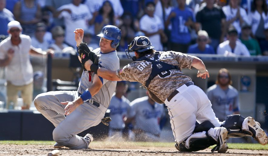 San Diego Padres catcher Yasmani Grandal puts tag on Los Angeles Dodgers' A.J. Ellis who is out trying to score in the eighth inning of a baseball game Sunday, Aug. 31, 2014, in San Diego.  (AP Photo/Lenny Ignelzi)