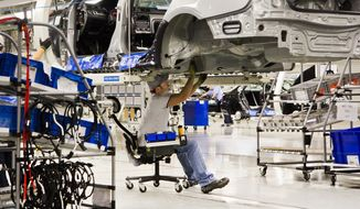 FILE - In this July 31, 2012, file photo, an employee works on a Passat sedan at the Volkswagen plant in Chattanooga, Tenn. Friday, Feb. 28, 2014, marks the end of the two-week period within which U.S. Sen. Bob Corker promised Volkswagen would announce another line at its factory in Tennessee if workers there rejected representation by the United Auto Workers union. So far there's little sign of any pending announcement.  (AP Photo/Erik Schelzig, File)