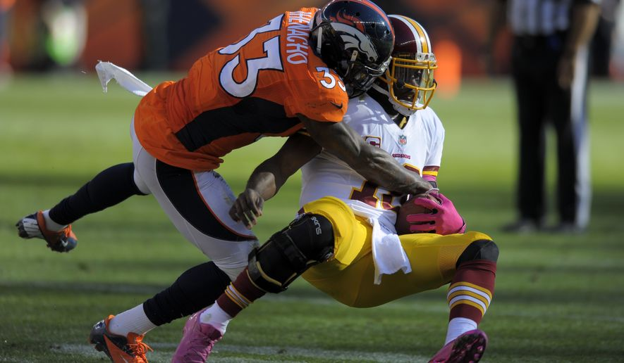 Washington Redskins quarterback Robert Griffin III is tackled by Denver Broncos strong safety Duke Ihenacho (33) during an NFL football game Sunday, Oct. 27, 2013, in Denver. (AP Photo/Jack Dempsey)