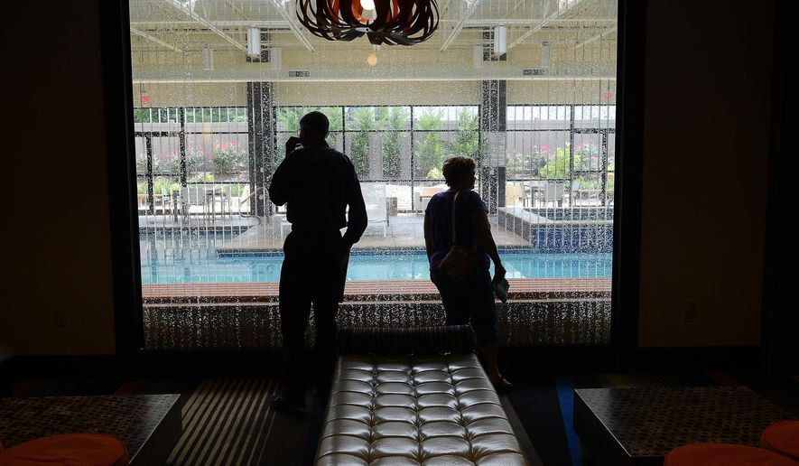 ADVANCE FOR MONDAY AUG. 31, AND THEREAFTER - This photo taken on Friday Aug. 15, 2014, shows guests of the Holiday Inn & Suites Charleston West as they check out the lobby and pool area in Charleston, W.Va. (AP Photo/The Charleston Gazette,  F. Brian Ferguson)