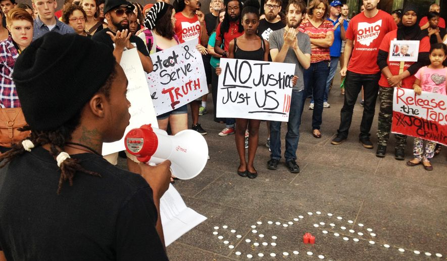 FILE - In this Aug. 5, 2014 file photo, members of the Ohio Student Association gather outside Ohio Attorney General Mike DeWine's office in Columbus, Ohio, to call for the release of in-store video in the fatal police shooting. Organizers told the Dayton Daily News they want to see what happened on Aug. 5 when 21-year-old John Crawford III was fatally shot by police. Officers said he refused to drop an air rifle inside a Wal-Mart store in Beavercreek. Details may differ, circumstances of their deaths may remain unknown, but the outrage that erupted after the Aug. 9 fatal shooting of the unarmed, black 18-year-old by a white officer in Ferguson, Missouri, has become a rallying cry in protests over police killings across the nation. (AP Photo/The Dayton Daily News, Jim Otte, File)