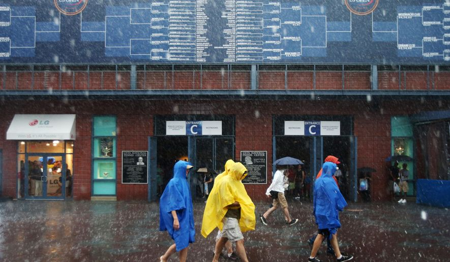 Tennis fans walk barefoot across the Billie Jean King National Tennis Center as rain falls suspending play during the 2014 U.S. Open tennis tournament, Sunday, Aug. 31, 2014, in New York. (AP Photo/John Minchillo)