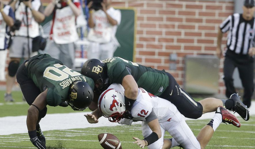 SMU quarterback Neal Burcham (12) fumbles the ball as he is hit by Baylor defensive lineman Beau Blackshear (95) and linebacker Aiavion Edwards (20) during the first half of an NCAA college football game Sunday, Aug. 31, 2014, in Waco, Texas.  The ball went out of bounds so SMU retained possession. (AP Photo/LM Otero)