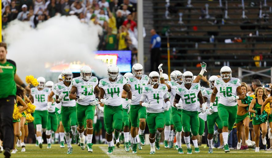 The Oregon football team runs onto the field for an NCAA college football game against South Dakota in Eugene, Ore., Saturday, Aug. 30, 2014. (AP Photo/Ryan Kang)