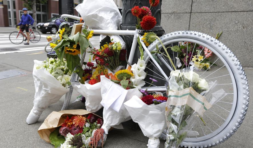 "A cyclist pauses near a white ""ghost bike"" memorial, Sunday, Aug. 31, 2014, in downtown Seattle where Sher Kung -- a well-respected attorney who was part of the American Civil Liberties Union's legal team that challenged the military's ""Don't Ask, Don't Tell"" policy -- was killed on her bike Friday in a collision with a truck. (AP Photo/Ted S. Warren)"