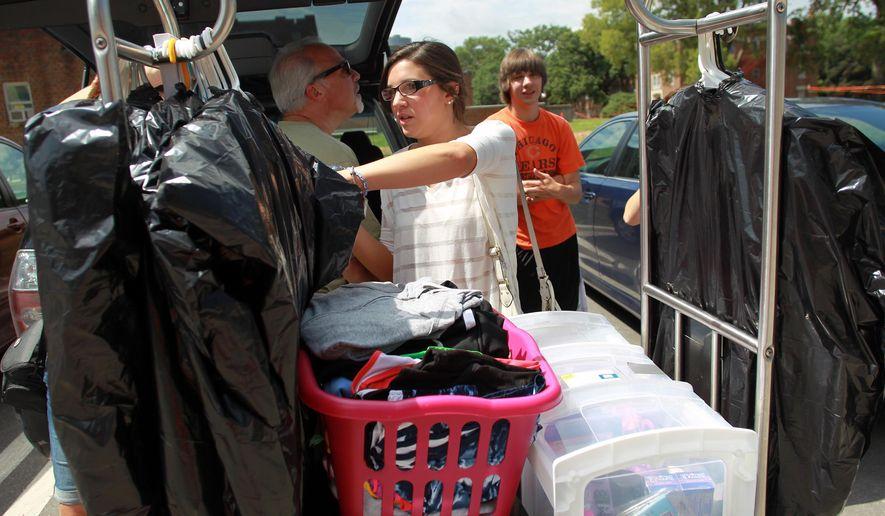 ADVANCED FOR RELEASE SUNDAY, AUGUST 31, 2014 University of Iowa freshman Michelle Castellani of Lake Zurich, Ill. unloads her family's car on Friday, Aug. 22, 2014. (AP Photo/Iowa City Press-Citizen, David Scrivner)