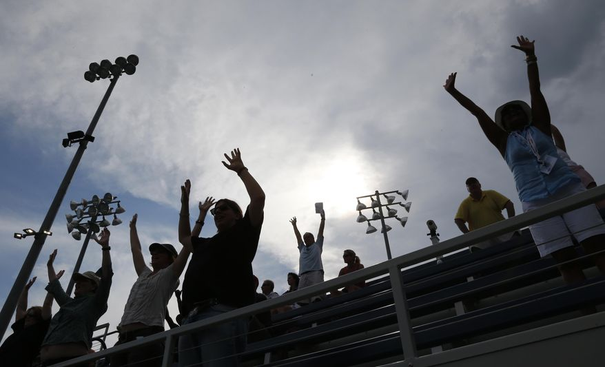 Fans cheer play as storm clouds begin to roll over the Billie Jean King National Tennis Center during the 2014 U.S. Open tennis tournament, Sunday, Aug. 31, 2014, in New York. (AP Photo/Elise Amendola)
