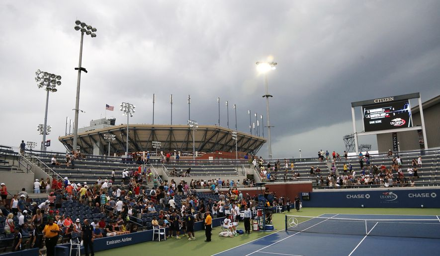 Play is suspended as storm clouds roll over the Billie Jean King National Tennis Center because of imminent lighting during the 2014 U.S. Open tennis tournament, Sunday, Aug. 31, 2014, in New York. (AP Photo/Elise Amendola)