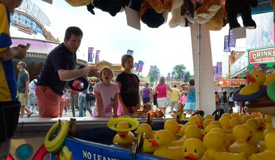 Brian Kamoie, 43, of Annapolis, Md concentrates as he attempts to get a ring around a floating ducky's neck while his daughters Julia and Cara look on at the Maryland State Fair in Timonium, Md on Sunday, August 31. Khalid Naji-Allah/Special to The Washington Times