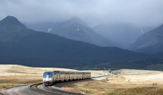 FILE - In this Sept. 18, 2011 file photo, Amtrak's Empire Builder rounds a turn near East Glacier Park, Mont. The U.S. Bureau of Land Management says it made a mistake giving active railroads too much discretion on what can be built on 200-foot-wide rights-of-way crossing thousands of miles of public land in 11 western states.  (AP Photo/Flathead Beacon, Justin Franz, File)