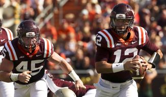 Virginia Tech quarterback Michael Brewer (12) runs up field after escaping William & Mary defender Luke Rhodes (50) during first half action of the Virginia Tech - William & Mary NCAA college football game in Blacksburg Va. Saturday, Aug. 30 2014. (AP Photo / The Roanoke Times, Matt Gentry)