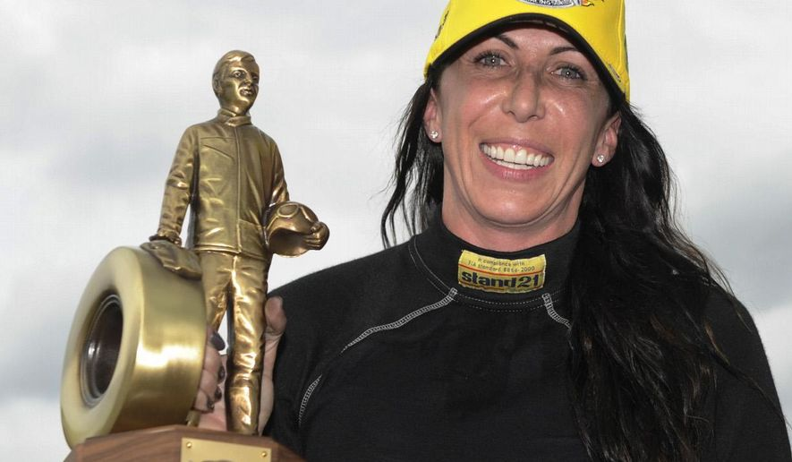 In this photo provided by NHRA, Alexis DeJoria holds her trophy Monday Sept. 1, 2014, in Brownsurg, Ind., after racing to the Funny Car victory at the 60th annual Chevrolet Performance U.S. Nationals at Lucas Oil Raceway.  DeJoria, is the fourth female to win the event in NHRA history.  (AP Photo/Jerry Foss)