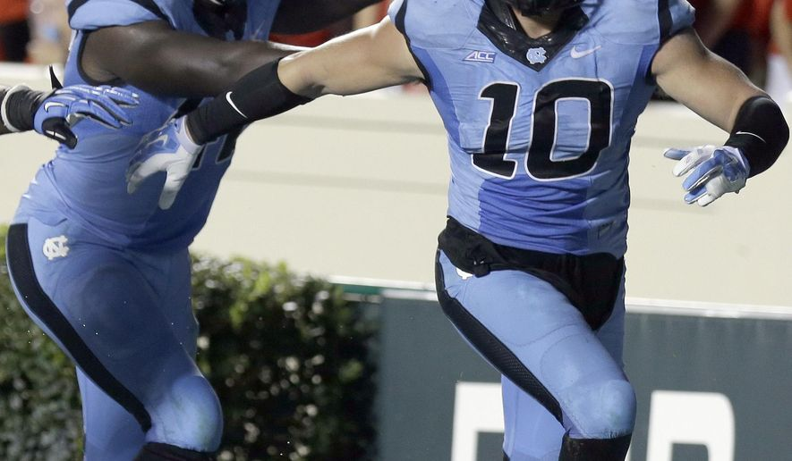 North Carolina's Shakeel Rashad and Jeff Schoettmer (10) celebrate Schoettmer's interception and touchdown against Liberty during the second half of an NCAA college football game in Chapel Hill, N.C., Saturday, Aug. 30, 2014. North Carolina won 56-29. (AP Photo/Gerry Broome)