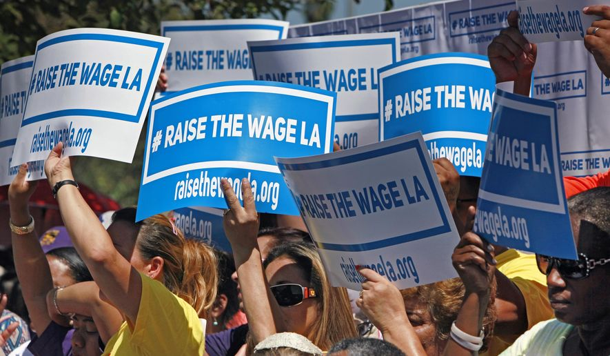 Supporters carry signs to raise the minimum wage in Los Angeles as they listen to Mayor Eric Garcetti during an announcement at  the Martin Luther King, Jr. Park with a coalition of business, labor, community, and faith leaders from across the city on Monday, Sept. 1, 2014. Garcetti announced his proposal to raise the minimum wage in Los Angeles from the current $9 per hour to $13.25 in 2017. (AP Photo/Richard Vogel)