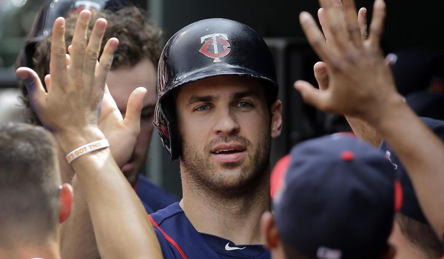 Minnesota Twins' Joe Mauer high-fives teammates in the dugout after scoring on a Kennys Vargas sacrifice fly ball in the sixth inning of a baseball game against the Baltimore Orioles, Monday, Sept. 1, 2014, in Baltimore. (AP Photo/Patrick Semansky)