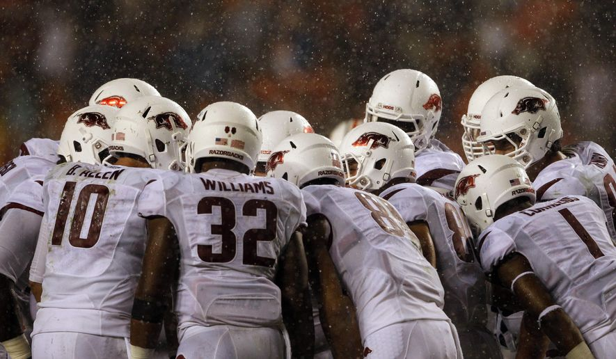 Arkansas huddles up before a play as the rain falls during the second half of an NCAA college football game against Auburn on Saturday, Aug. 30, 2014, in Auburn, Ala. Auburn defeated Arkansas 45-21. (AP Photo/Butch Dill)