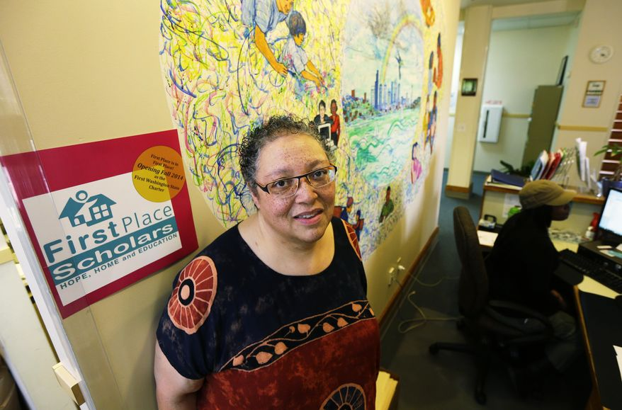In this photo taken June 18, 2014, Sheri Day, acting executive director of First Place Scholars Charter School poses for a photo near a mural behind the school's reception desk in Seattle. On Wednesday, Sept. 3, 2014, the former private school will open its doors as Washington's first public charter school. (AP Photo/Ted S. Warren)