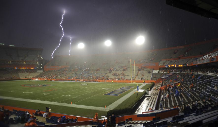 Lightning strikes near Ben Hill Griffin Stadium at Florida Field during a weather delay before an NCAA college football game between Florida and Idaho in Gainesville, Fla., Saturday, Aug. 30, 2014. (AP Photo/Phil Sandlin)