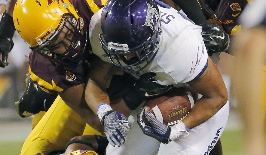 Weber State running back Zach Smith is stopped by Arizona State players during the second half of an NCAA college football game, Thursday, Aug. 28, 2014, in Tempe, Ariz. (AP Photo/Matt York)