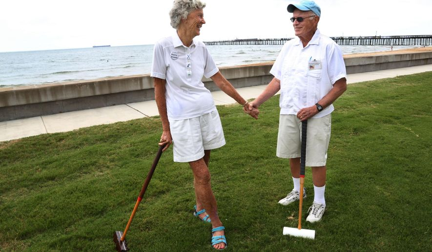 Penny and Ty Brown stand near the seawall at Westminster-Canterbury in Virginia Beach, Va. after playing in a croquet tournament on Saturday morning, Aug. 23, 2014. The Browns have called this retirement place home since July 2004, when they traded their three-bedroom Chicago estate for a smaller apartment with one bedroom. (AP Photo/The Virginian-Pilot, Martin Smith-Rodden)