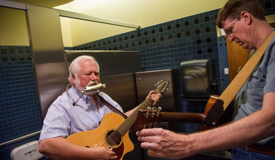 Dave Law (left) and Ben Hamblin tune up and prepare for their open mic song in the restroom. (Photographs by Rod Lamkey Jr./Special to the Washington Times)