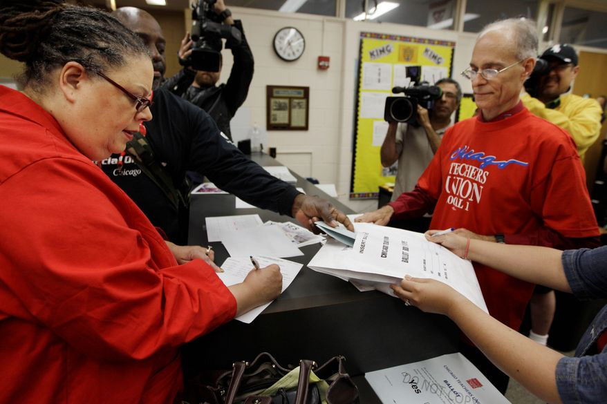 Chicago Teachers Union President Karen Lewis (left) registers for her ballot during a strike authorization vote at a high school in Chicago in 2012. Illinois Gov. Pat Quinn pushed through legislation aimed at overhauling the pension fund last year, but organized labor brought a court challenge to stymie that process. (Associated Press)