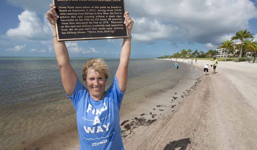 In this photo provided by the Florida Keys News Bureau, Diana Nyad poses with a bronze plaque Monday, Sept. 1, 2014, at Smathers Beach in Key West, Fla. The plaque commemorates Nyad's 2013 Cuba-to-Florida Keys swim. She arrived at Smathers Beach the early afternoon of Sept. 2, 2013, to become the first person to ever swim  from Havana to Key West without a shark cage. (AP Photo/Florida Keys News Bureau, Andy Newman)