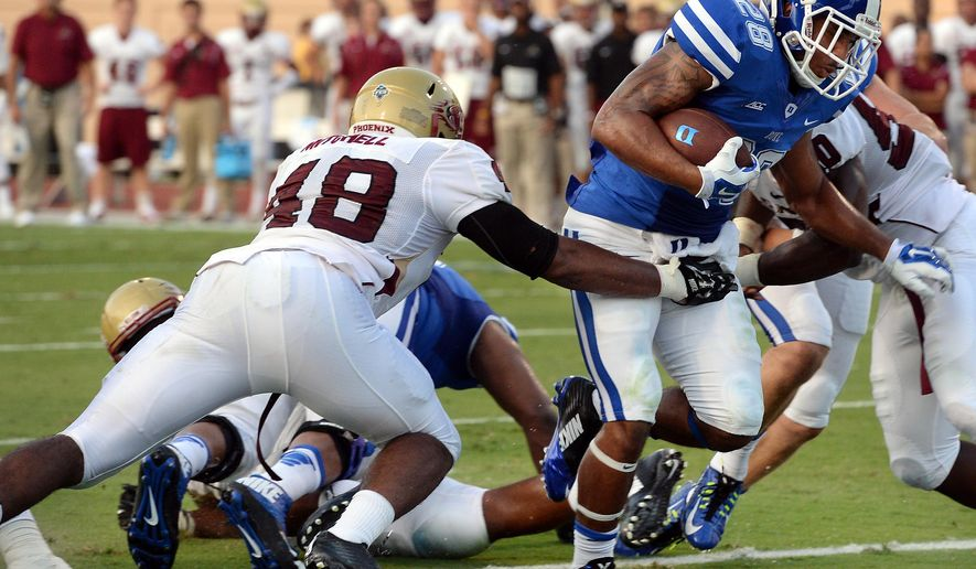 Duke running back Shaquille Powell (28) scores a second-quarter touchdown as Elon linebacker Corey Mitchell (48) during an NCAA college football game Saturday, Aug. 30, 2014, in Durham, N.C. Duke won 52-13. (AP Photo/The News & Observer, Chuck Liddy)