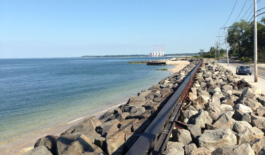 In this Aug. 26, 2014 photo, a sea wall separates Asharoken Village, N.Y. from Long Island Sound. The wall was washed over during Superstorm Sandy in October 2012, causing erosion and and taking down power lines. Asharoken can accept federal aid to build a dune and create public access to its beach for the first time in nearly 90-year history. Or it can reject aid, retain its private beach and allow erosion and other issues to worsen. (AP Photo/Emily Dooley)