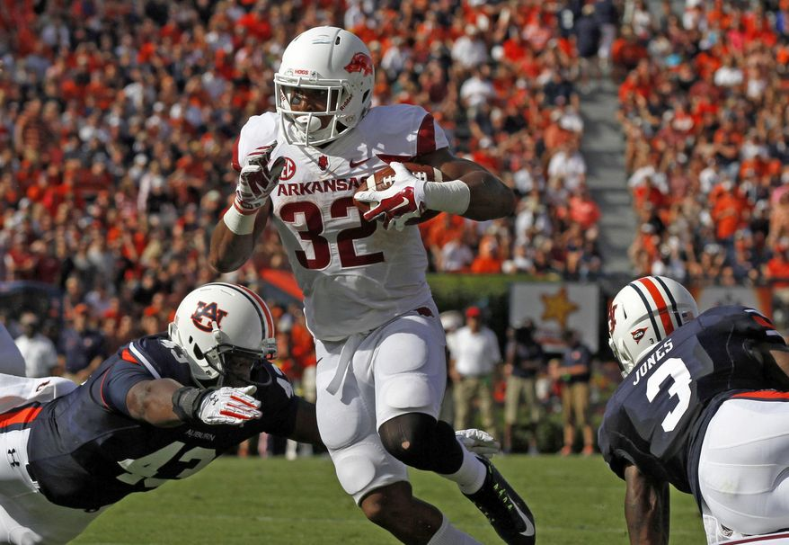 Arkansas running back Jonathan Williams (32) gets by Auburn linebacker Anthony Swain (43) and goes in for a touchdown during the first half of an NCAA college football game on Saturday, Aug. 30, 2014, in Auburn, Ala. (AP Photo/Butch Dill)