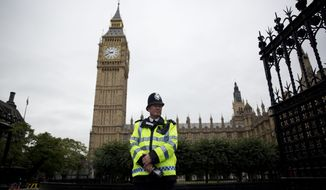 A British police officer stands guard outside the Houses of Parliament in London, Monday, Sept. 1, 2014.  Britain's Prime Minister David Cameron is expected on Monday to expand powers to combat terrorism in hopes of preventing attacks by Islamist militants returning from terror training in the Middle East.  (AP Photo/Matt Dunham)