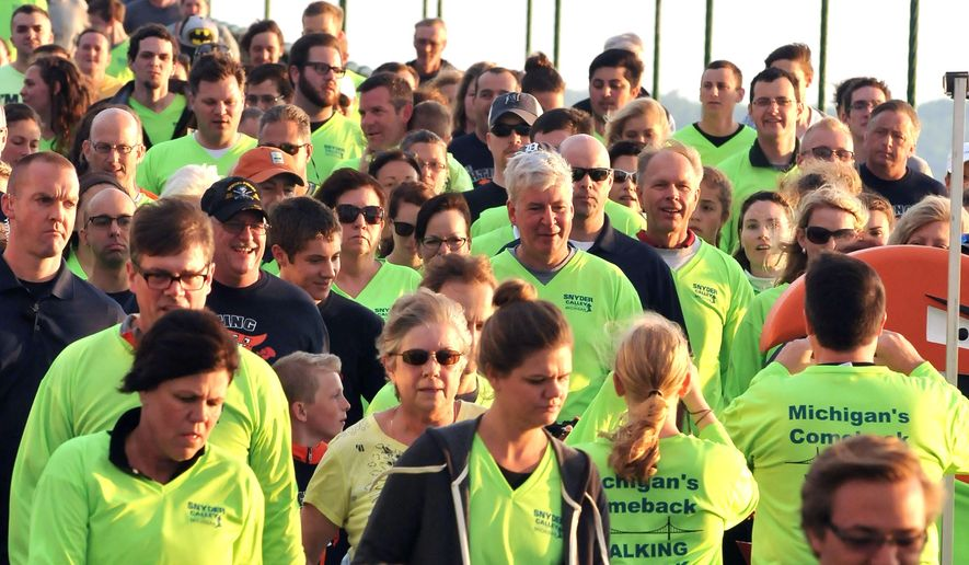 Michigan Gov. Rick Snyder, center, leads thousands of walkers across the five-mile-long Mackinac Bridge, Monday, Sept. 1, 2014 during the 57th annual Labor Day walk. Thousands cross from the upper peninsula of Michigan to the lower peninsula, the only day pedestrians are allowed on the span. (AP Photo/John L. Russell)