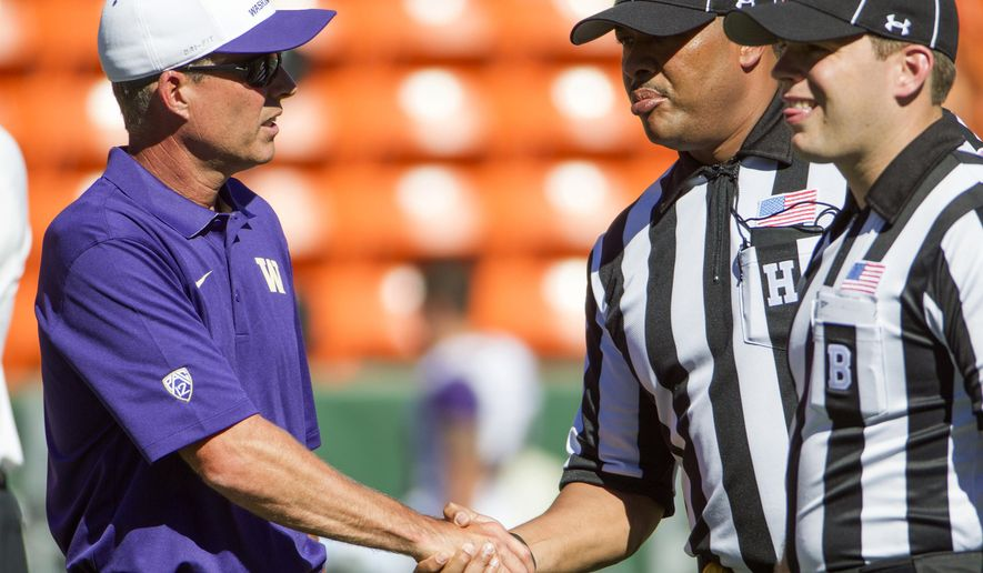 Washington coach Chris Petersen, left, shakes hands with a game official before an NCAA college football game against Hawaii, Saturday, Aug. 30, 2014, in Honolulu. (AP Photo/Eugene Tanner)