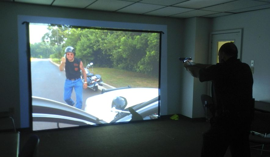 ADVANCE FOR MONDAY, SEPT. 1, 2014 AND THEREAFTER - In this Aug. 7, 2014, photo, Front Royal police Capt. Jason Ryman practices his shooting and decision making skills on a newly acquired firearms simulator in Front Royal, Va.  (AP Photo/ Northern Virginia Daily, Joe Beck)