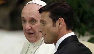 Pope Francis talks to former Argentine defender Javier Zanetti in the Paul VI hall at the Vatican, Monday, Sept. 1, 2014 ahead of an inter-religious match for peace. The friendly soccer match, supported by Pope Francis to promote the dialogue and peace among different religions, is scheduled at Rome's Olympic stadium later Monday. (AP Photo/Gregorio Borgia)