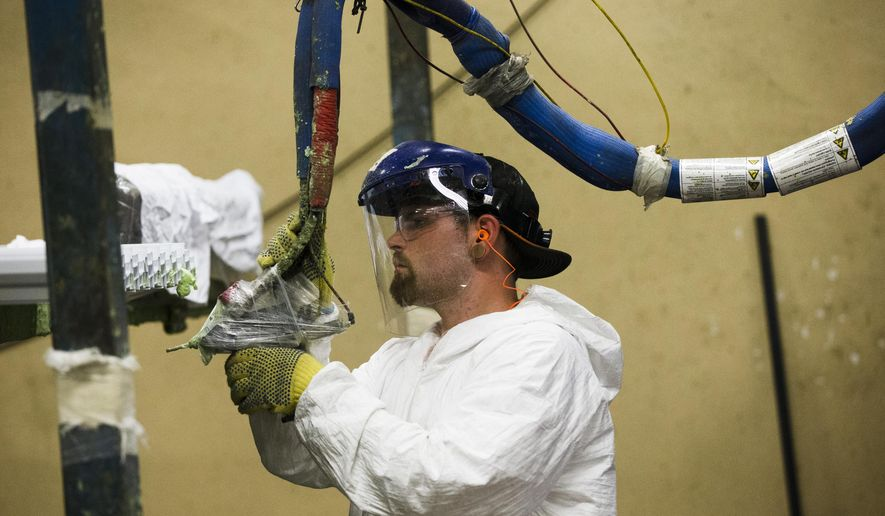 In this Aug. 7, 2014 photo, a worker assembles construction supplies at Northeast Building Products in Philadelphia. The Institute for Supply Management, a trade group of purchasing managers, issues its index of manufacturing activity for August on Tuesday, Sept. 2, 2014. (AP Photo/Matt Rourke)