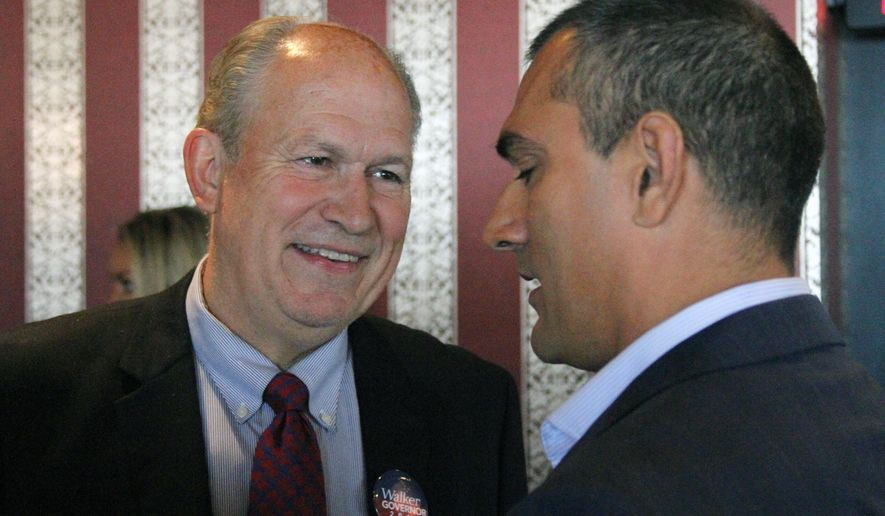 Alaska gubernatorial candidate Bill Walker, left, talks with his former running mate, Craig Fleener, before a news conference, Tuesday, Sept. 2, 2014, in Anchorage, Alaska. Walker will join with the former Democratic gubernatorial candidate, Byron Mallott, in a unified ticket to face Republican Gov. Sean Parnell in the general election.  Fleener stepped aside to let Mallott be the lieutenant governor candidate. (AP Photo/Mark Thiessen)