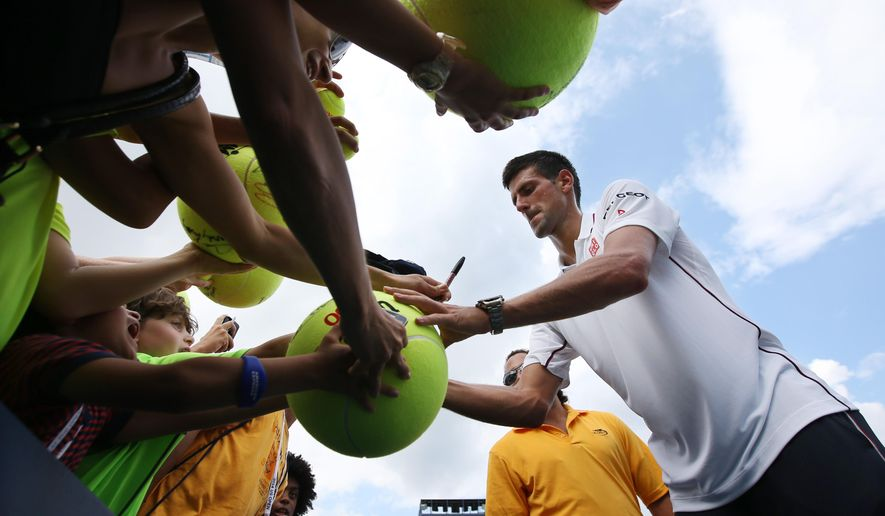 Novak Djokovic, of Serbia, signs autographs for fans after defeating Philipp Kohlschreiber, of Germany, during the fourth round of the 2014 U.S. Open tennis tournament, Monday, Sept. 1, 2014, in New York. (AP Photo/John Minchillo)