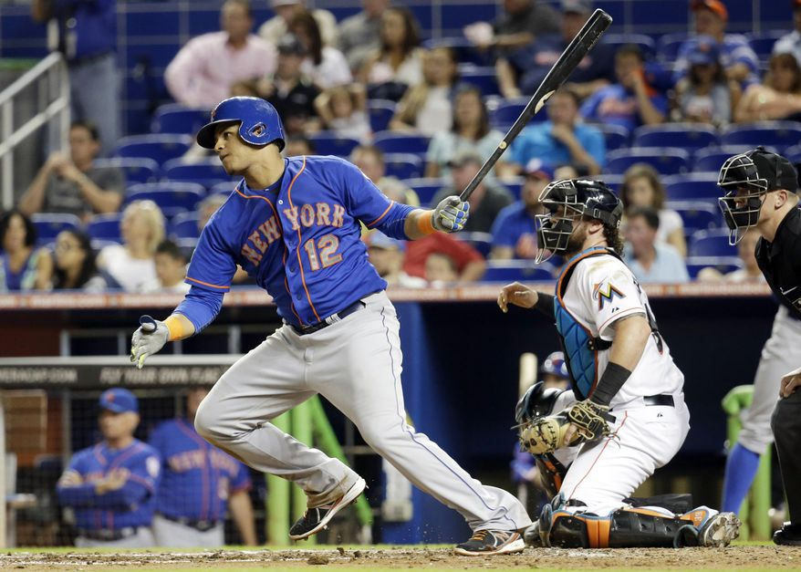 New York Mets' Juan Lagares (12) watches after hitting a RBI singe to score Wilmer Flores in the fourth inning during a baseball game, Tuesday, Sept. 2, 2014, in Miami. At right is Miami Marlins catcher Jarrod Saltalamacchia. (AP Photo/Lynne Sladky)