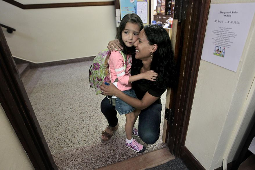 In this photo taken on Wednesday, Aug. 27, 2014, Tia Bastian gives her daughter Avery, 5, a hug before going into Dana Elfering's class for the first day of kindergarten in Minneapolis. (AP Photo/The Star Tribune, Elizabeth Flores)  MANDATORY CREDIT; ST. PAUL PIONEER PRESS OUT; MAGS OUT; TWIN CITIES LOCAL TELEVISION OUT