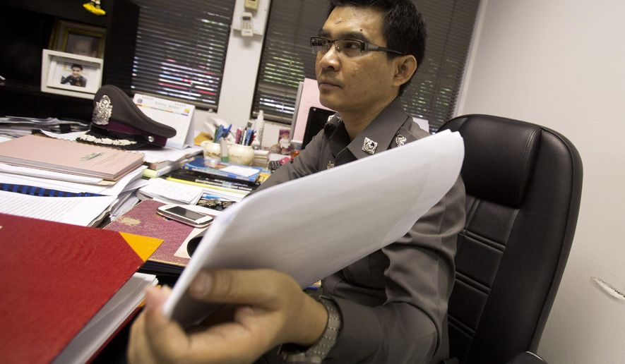 In this Aug. 26, 2014 photo, Police Col. Decha Promsuwan, an investigator in a surrogacy scandal involving a Japanese businessman, shows documents during an interview at Lumpini police station in Bangkok,Thailand. Wassana, a young Thai woman, answered an online ad offering $10,000 for surrogate mothers and is now embroiled in the case of a mysterious Japanese man, Mitsutoki Shigeta, who police say fathered at least 16 children through surrogates. The case has captivated Thailand and is at the center of a growing scandal over commercial surrogacy, an industry that thrived on semi-secrecy and legal loopholes that the country's military government now vows to ban. (AP Photo/Sakchai Lalit)