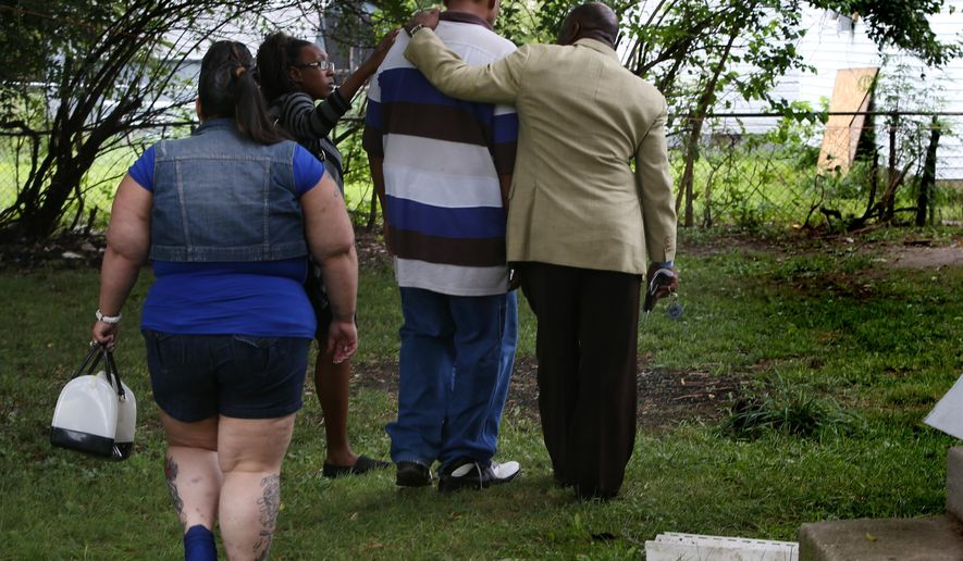 IMPD Chaplain David Coatie, right, supports Louis Allen, center, father of 15-year-old Dominique Allen, whose badly burned body was discovered in a backyard in Indianapolis on Sunday, as they walk back to the site where her body was found, Tuesday, Sept. 2, 2014. Dominique's purse and shoes were found about a block away from where her body was found. The Marion County Coroner's Office ruled the death, by asphyxiation, a homicide. Dominique Allen was a Ben Davis freshman. (AP Photo/The Indianapolis Star, Charlie Nye)