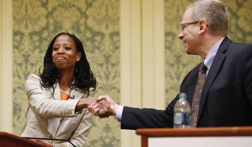 FILE - In this May 20, 2014 file photo, Republican Mia Love, left, and Democrat Doug Owens shake hands after a debate in Salt Lake City. The state's most high-profile political race this year will soon spill onto Utah televisions. Love and Owens have spent a combined half a million dollars on campaign ads set to start airing Sept. 15. (AP Photo/The Deseret News, Jeffrey D. Allred, File)
