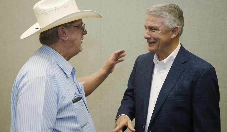 Nashville, Ark., cattle farmer Jerry Christie, left, talks with Democratic Congressional candidate James Lee Witt after an agricultural forum in Hot Springs, Ark., Tuesday, Sept. 2, 2014. Witt will face Repubican candidate Bruce Westerman in the November election. (AP Photo/Danny Johnston)