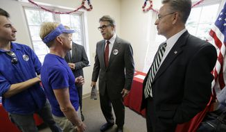 Texas Gov. Rick Perry, center, speaks to local residents while campaigning for 1st Congressional District candidate Rod Blum, right, Tuesday, Sept. 2, 2014, in Cedar Rapids, Iowa. (AP Photo/Charlie Neibergall) **FILE**