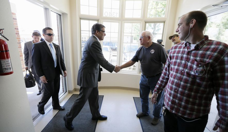 Texas Gov. Rick Perry is greeted by local residents while campaigning for 1st Congressional District candidate Rod Blum, Tuesday, Sept. 2, 2014, in Cedar Rapids, Iowa. (AP Photo/Charlie Neibergall)