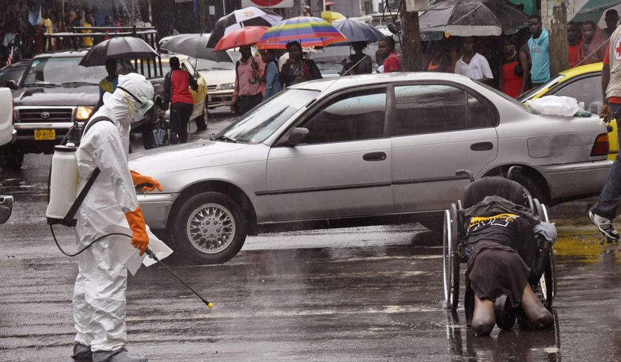 Health workers spray the body of an amputee suspected of dying from the Ebola virus with disinfectant, in a busy street in Monrovia, Liberia, Tuesday, Sept. 2, 2014.  Food in countries hit by Ebola is getting more expensive and will become scarcer because many farmers won't be able to access fields, a U.N. food agency warned Tuesday. An Ebola outbreak in West Africa has killed more than 1,500 people, and authorities have cordoned off entire towns in an effort to halt the virus' spread.  (AP Photo/Abbas Dulleh)