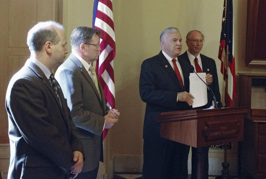 Republican State Rep. Matt Lynch, second from right, announces plans to force the Ohio House to vote on a bill that would require voters to show photo identification at the polls in Columbus, Ohio on Tuesday, Sept. 2, 2014. State lawmakers are on summer break, and it is uncertain whether the effort will be successful. (AP Photo/Ann Sanner)